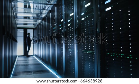 Photo of Out of Focus IT Technician Turning on Data Server. Royalty-Free Stock Photo #664638928