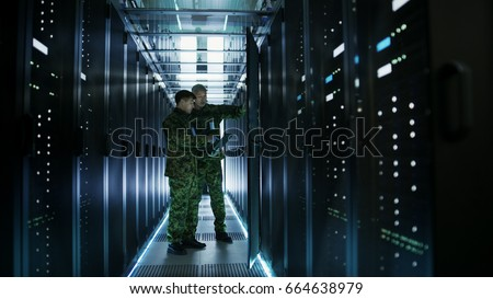 In Data Center Two Military Men Work with Open Server Rack Cabinet. One Holds Military Edition Laptop. #664638979