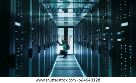 A Hooded Hacker With Laptop Connects to Rack Server and Steals Information from Corporate Data Center. #664640128