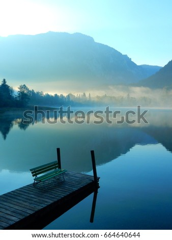 A beautiful view of a wooden bench on a deck in a sunrise mist at a gorgeous lake in Austria #664640644