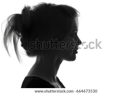 Black and white trendy portrait profile silhouette of face of a beautiful young woman with a hairdo on her head #664673530