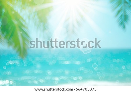 Blur beautiful nature green palm leaf on tropical beach with bokeh sun light wave abstract background. Vintage tone color style.