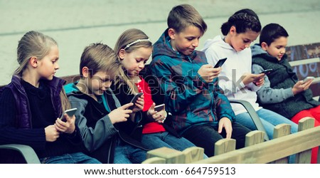 children posing at urban street with mobile devices outdoors #664759513
