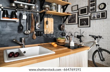 Design of modern home kitchen in the loft and rustic style. Black wall with shelves, trays, jars, mugs, sink. Against a wall with photos of a couple and a mountain bike.