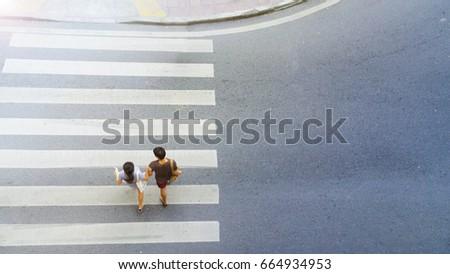 Top view of couple man and women people walk across crosswalk in the city street.  #664934953