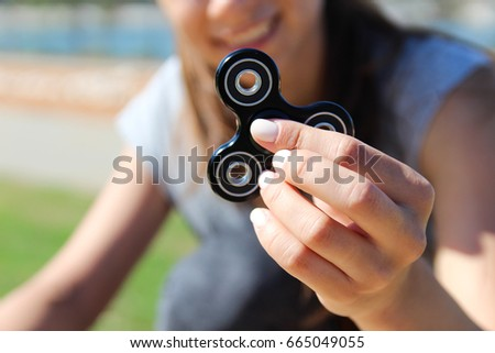 Women and men hold a white and black spinner  #665049055