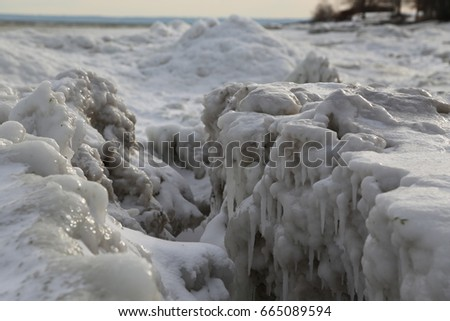 Crevasse in pack ice on the shoreline of a body of water during a very cold period in winter. #665089594