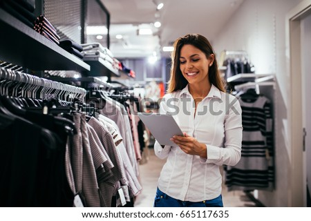 Beautiful woman using tablet while working in the store. Royalty-Free Stock Photo #665117635