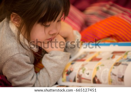 Young Japanese Girl reading a coming book on her bed. Royalty-Free Stock Photo #665127451