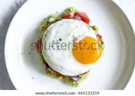 egg sunny side up on a bed of guacamole  egg sunny side up on tomato tartar with avocado #665133259