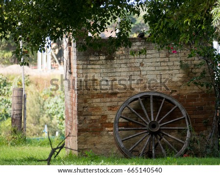 Old fashioned wagon wheel this brick wall background this Green grass and shrubs around #665140540