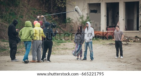 Behind the scene. Film crew team filming movie scene on outdoor location. Group cinema set