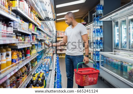 African man shopping in beverage section at supermarket. Black man doing shopping at market while buying cold drink. Handsome guy holding shopping basket reading nutritional values of product. #665241124