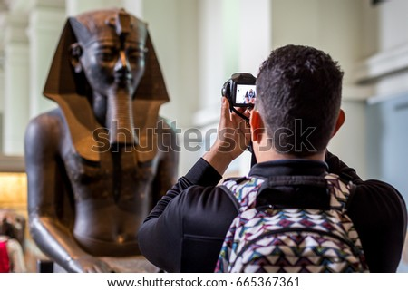 A tourist taking photo of an egyptian status brought from Egypt and kept in British Museum of London