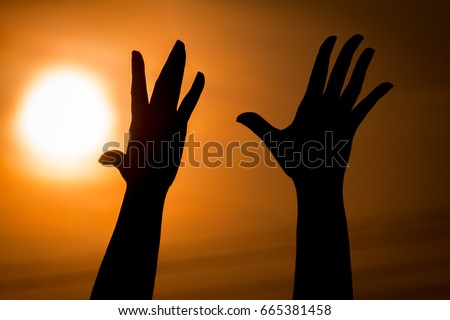 Silhouettes of hands young woman on sky with sunset background, for hope or despair concept.  #665381458