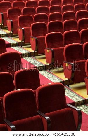 red velvet seats for spectators in the theater or cinema #665423530