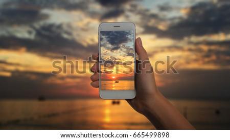 Hands holding phone take a photo beach night sunrise