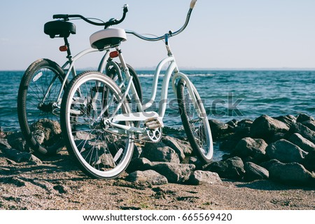 Two retro bike on the beach against the blue sea on a sunny day #665569420