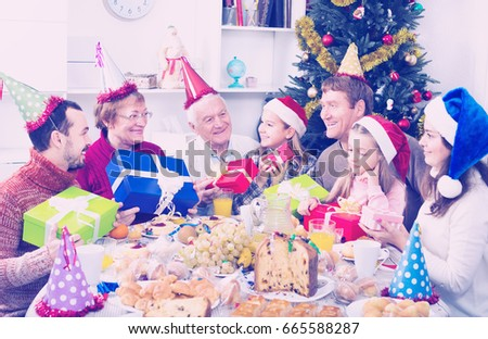 Large family handing a gifts to each other during Christmas dinner #665588287