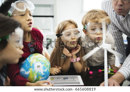 Diverse kindergarten students learning energy producer from solar windmill in science class Royalty-Free Stock Photo #665608819