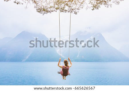 dream concept, beautiful young woman on the swing in fjord Norway, inspiring landscape Royalty-Free Stock Photo #665626567