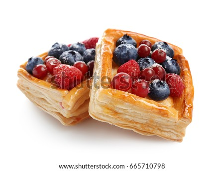 Delicious puff pastries with berries on white background Royalty-Free Stock Photo #665710798