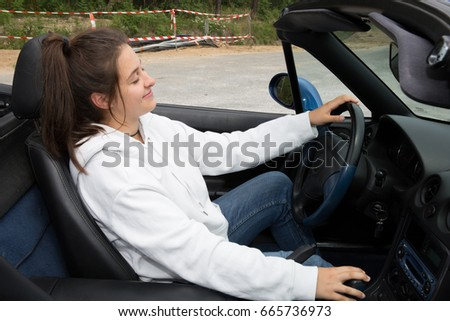 happy and relaxed girl at the wheel of her car #665736973