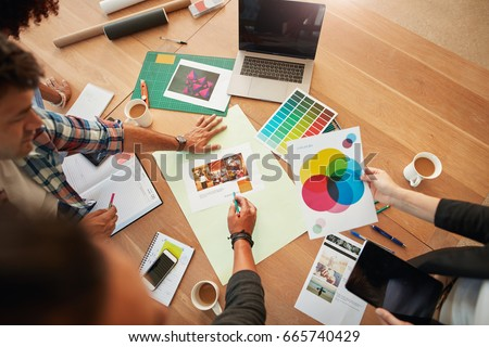 Top view shot of group of creative designers discuss the color palette during meeting. Creative team brainstorming around table. Royalty-Free Stock Photo #665740429