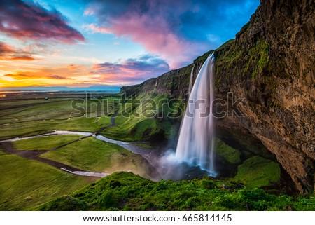 Seljalandsfoss - Seljalandsfoss is located in the South Region in Iceland right by Route 1. One of the interesting things about this waterfall is that visitors can walk behind it into a small cave.   Royalty-Free Stock Photo #665814145