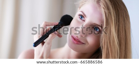 Pretty woman applying make up with brush #665886586