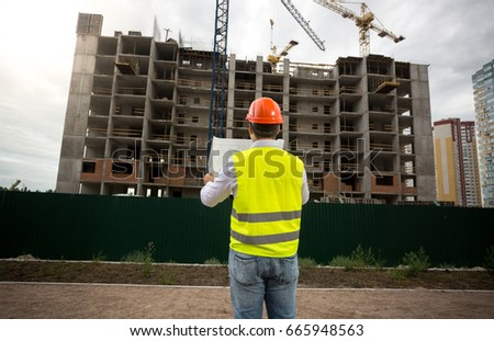 Young construction engineer reading blueprints at building site #665948563