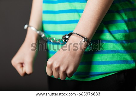 Close up on pair of hands from child or teenager in green and blue shirt tied with metal handcuffs Royalty-Free Stock Photo #665976883