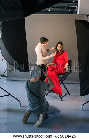 Photographer and stylist work in studio . Man taking shot of female model, visagist doing makeup. Creative team make commercials. Photo school, lookbook, fashion backstage concept