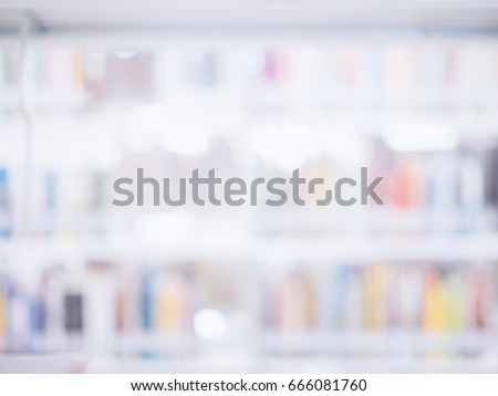 Blurred image of many books on bookshelf in library background.