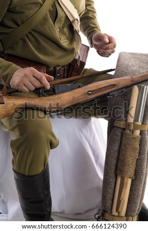Male actor in the form of ordinary soldiers of the Russian army during the First World War dismantles and collects a rifle against a white background #666124390