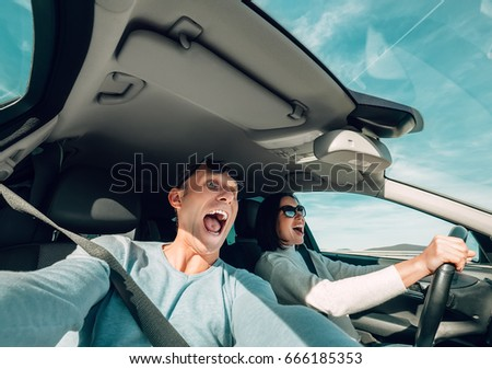 Screaming couple riding in car wide angle view #666185353