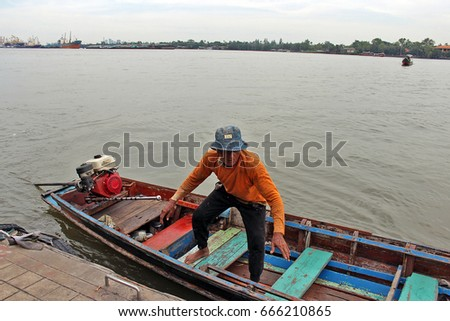 A local parking his motorized long-tailed boat by a pier to give commuters a ride across Chao Phraya river. (Bangkok, Thailand) 11/2015 #666210865