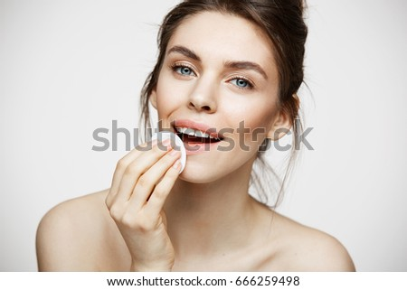 Cute beautiful natural brunette girl cleaning face with cotton sponge smiling looking at camera over white background. Cosmetology and spa. #666259498