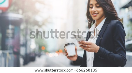 Professional business woman using technology outside, Professional female manager reading information in internet while walking outdoor #666268135