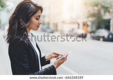 Successful female employer typing text message on her cellphone outdoor #666268189