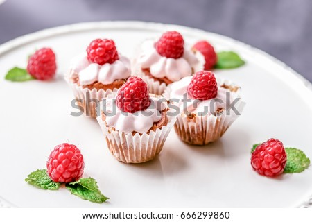 Four mini vanilla cupcakes with fresh lemonade buttercream and fresh raspberries served on a white round plate #666299860