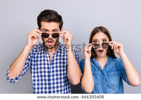 Oh really?! Wow! Two young shocked lovers are amazed with wide open eyes, mouthes, touching sun glasses, standing in a casual wear on light background