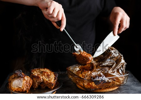 Man takes cooked pieces of marinated pork shoulder from roasting sleeve #666309286