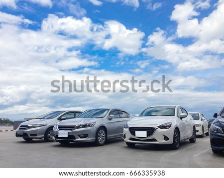 Car parked in parking lot at the rooftop of car parking building with white cloud and blue sky background #666335938