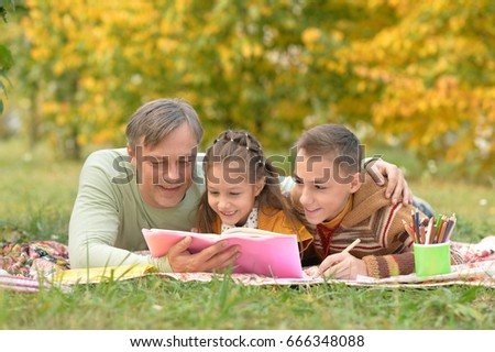 Family resting in park with  book #666348088