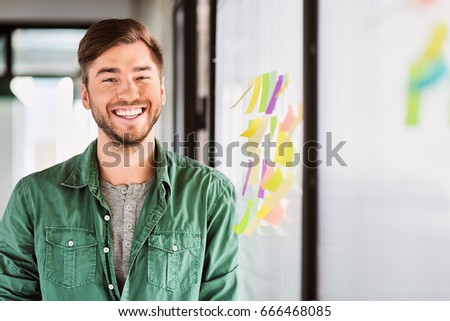 Happy young man working in office #666468085