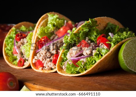 Photo of Mexican tacos with ground beef, onion, tomatoes, chili, red sauce, lettuce and lime on wooden background. Spicy and fast food concept. #666491110
