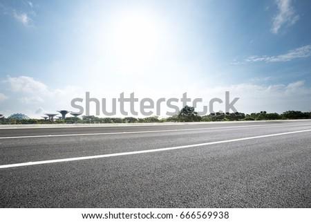 empty road near park with blue sunny sky #666569938