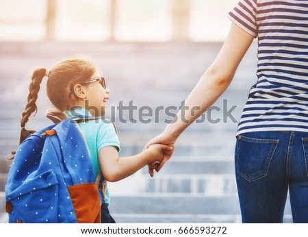 Parent and pupil of primary school go hand in hand. Woman and girl with backpack behind the back. Beginning of lessons. First day of fall. #666593272