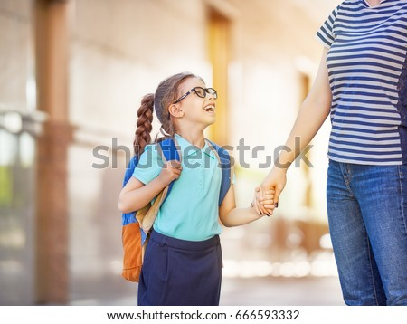 Parent and pupil of primary school go hand in hand. Woman and girl with backpack behind the back. Beginning of lessons. First day of fall. Royalty-Free Stock Photo #666593332